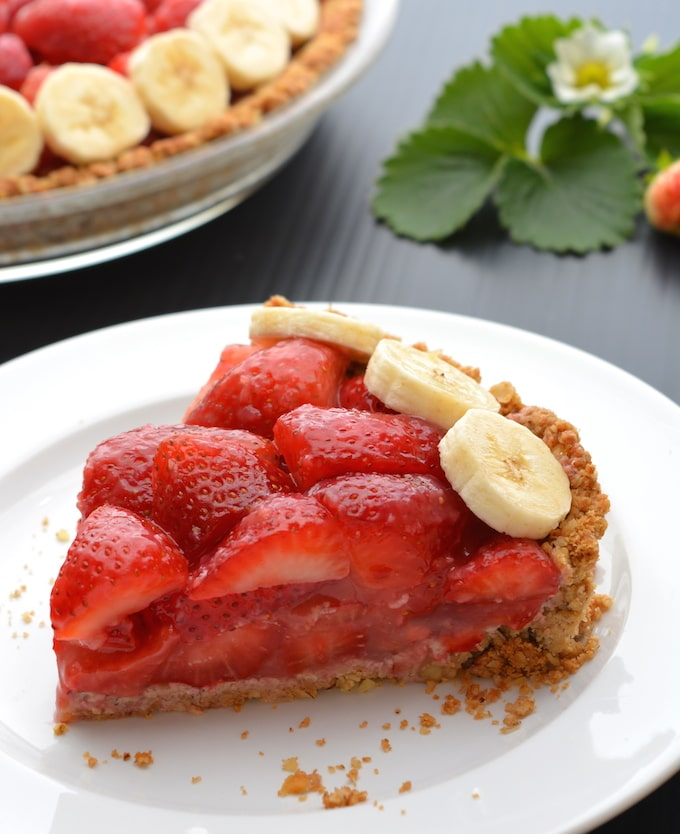 A piece of Vegan Strawberry Pie topped with banana slices on a white plate.