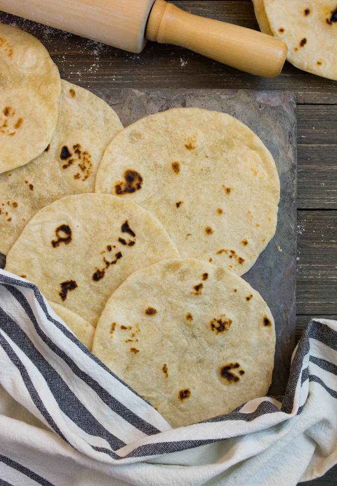 Finished, homemade Flour Tortillas keeping warm under a kitchen towel.