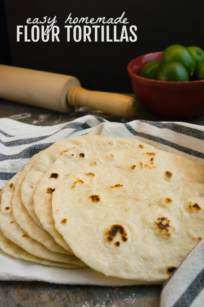 Homemade flour tortillas stacked on a kitchen towel.