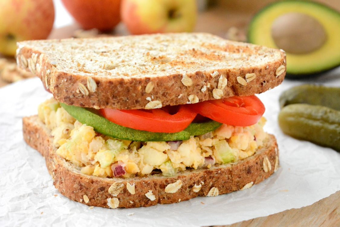 An apple-walnut chickpea salad sandwich topped with avocado and tomato slices. It's on white parchment paper. There are pickles, red and yellow gala apples, walnuts and half of an avocado in the back.