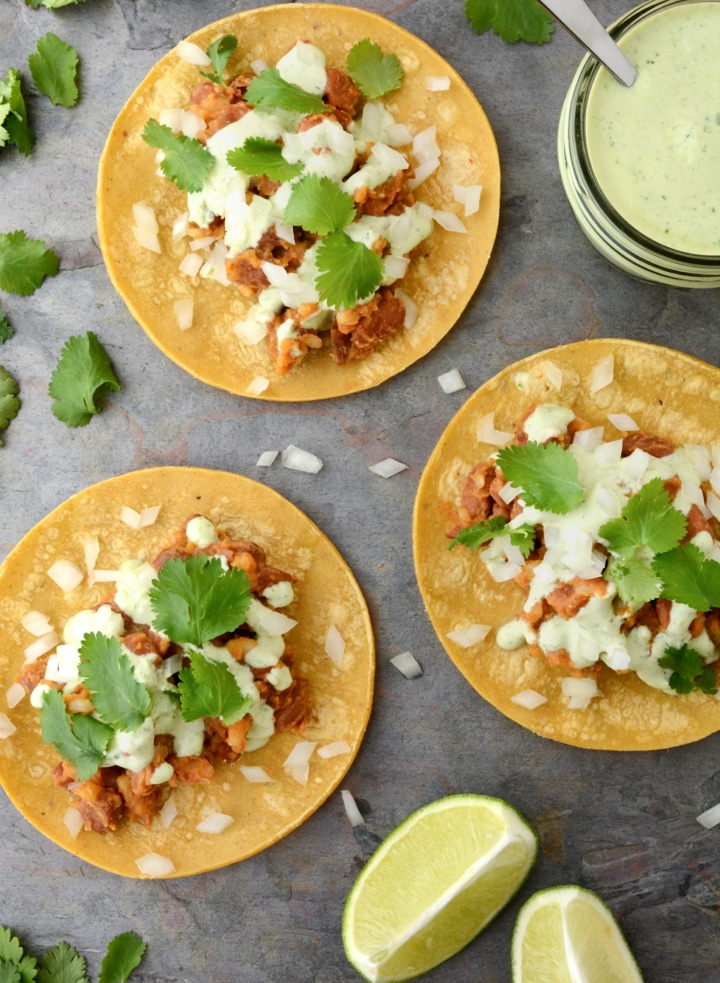 Vegan Tacos with Cilantro Lime Sauce are gluten-free and oil-free. These healthy 20 minute vegan tacos are so easy to make and only take one pan! The filling is made with seasoned pinto beans and rice. Then the tacos are topped with a tangy cilantro lime sauce.