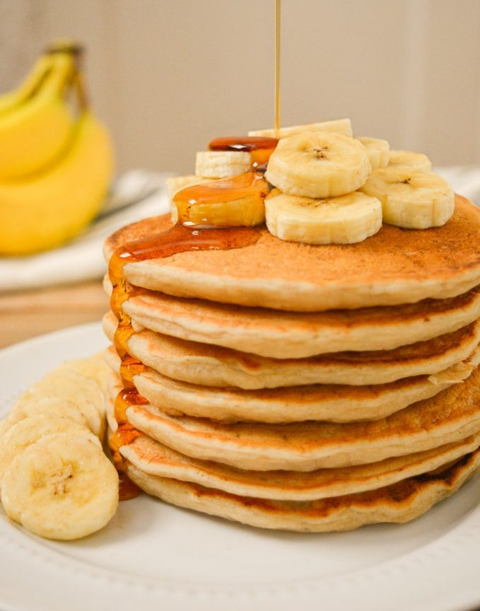 A stack of vegan banana milk pancakes with banana slices on top and syrup being poured on top.