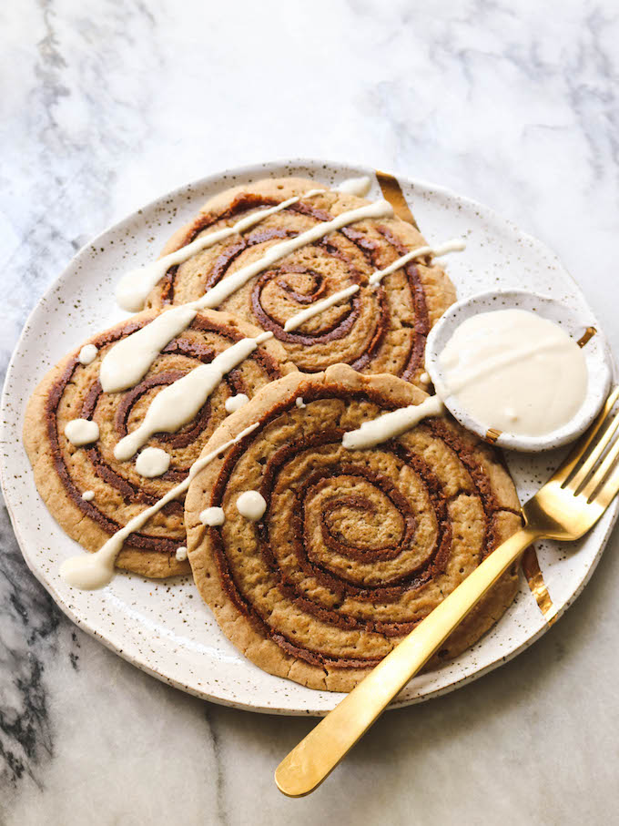 Vegan cinnamon roll pancakes topped with icing.