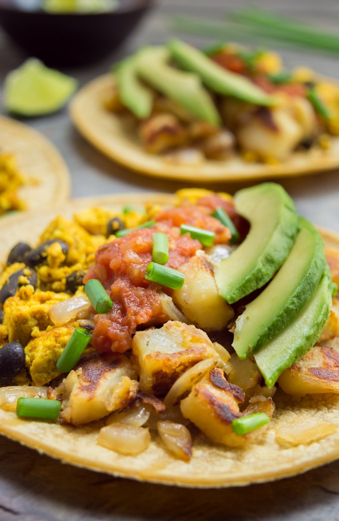 Vegan Breakfast Tacos- A corn tortilla filled with tofu scramble, black beans, breakfast potatoes, salsa, avocado slices and green onions.