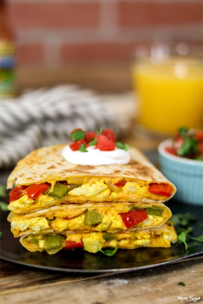 Vegan Breakfast Quesadilla cut into 3 triangles and stacked on a black plate.