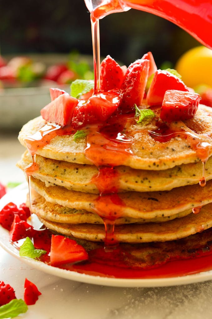 A stack of strawberry lemon pancakes topped with fresh strawberries.