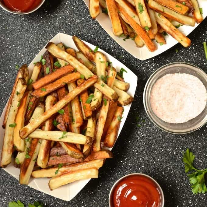 Baked fries in a fry boat with a side of ketchup and himalayan pink salt.