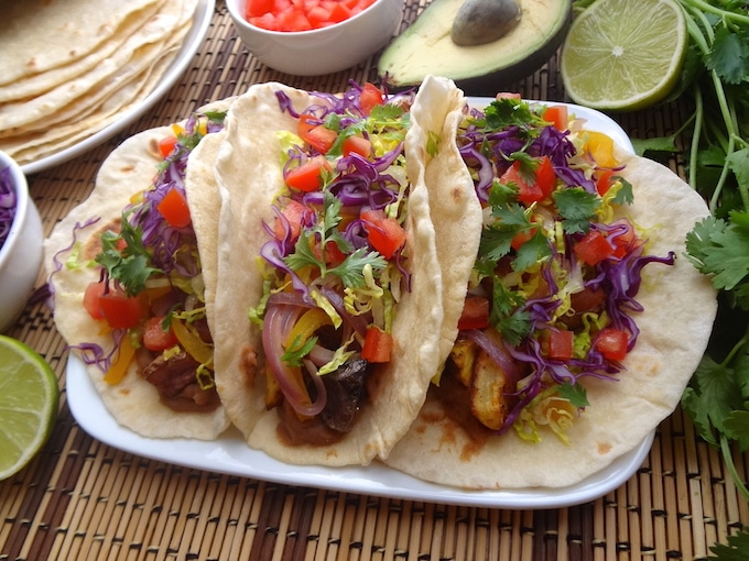 Siting on a tan and brown mat are 3 Vegan potato tacos on a plate. They're filled with seasoned refried beans, adobo seasoned potatoes, fajita style bell peppers and onions, fresh shredded purple cabbage and lettuce, and tomatoes. Around the potato tacos sits a lime wedge, bowl of purple cabbage, plate of fresh homemade tortillas, bowl of diced tomatoes, half an avocado, and fresh cilantro.