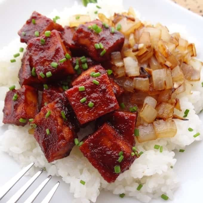 Square cuts of bbq tofu and caramelized onions on top a bed of white rice.