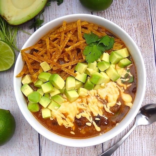 A bowl of vegan tortilla soup topped with cashew cheese, diced avocado, cilantro, and tortilla strips.