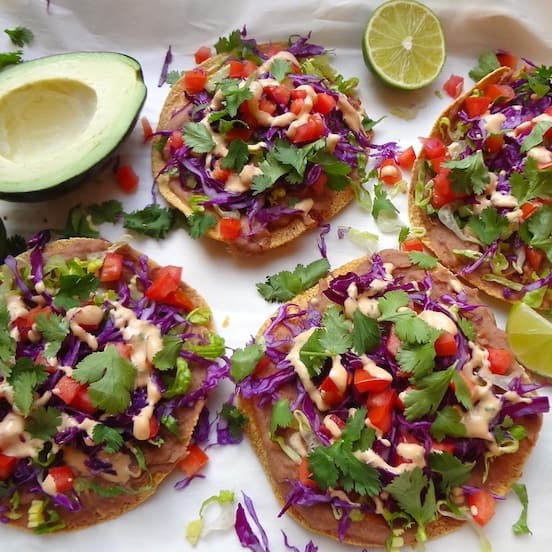 Four vegan tostadas on a sheet of parchment paper alongside an avocado and lime cut in half.