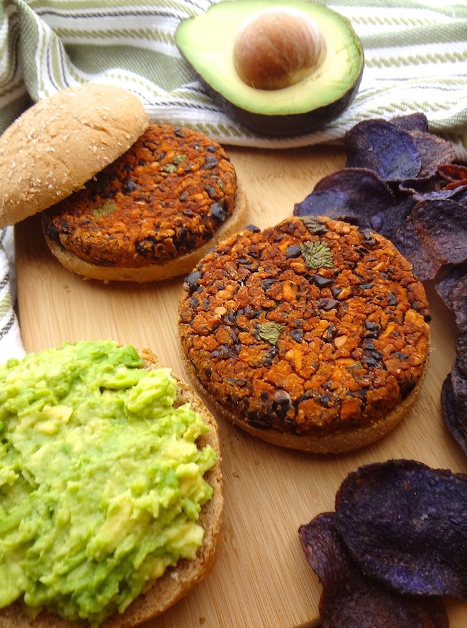 BBQ black bean burger topped with mashed avocado and served with a side of purple potato chips.