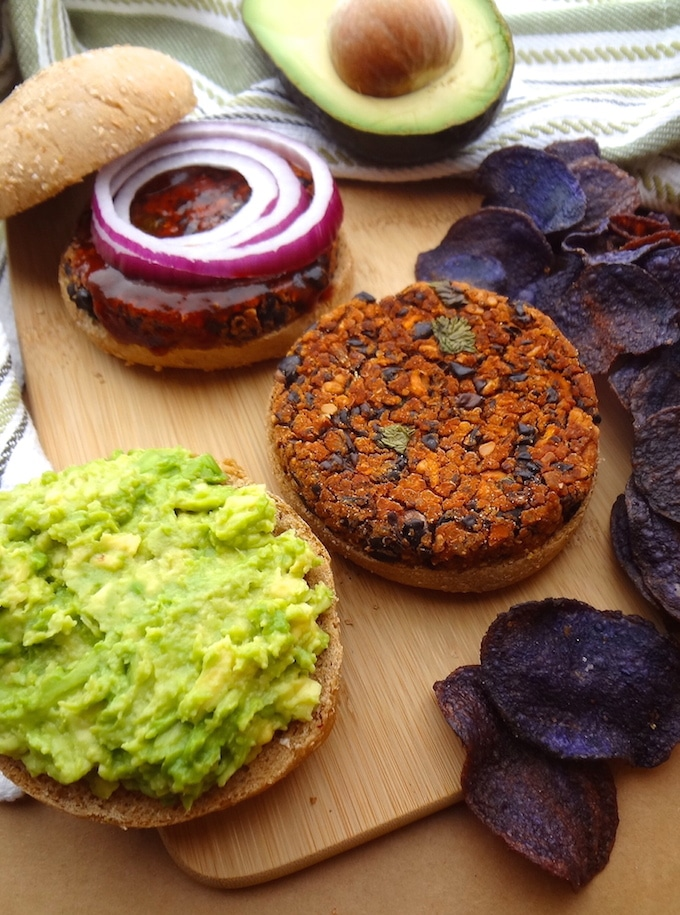 2 black bean burgers topped with avocado and red onion rings. Served with a side of purple potato chips.