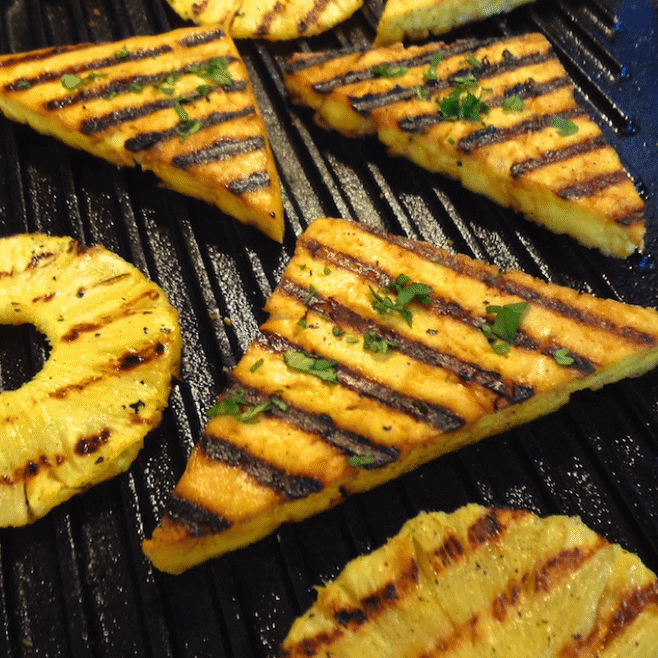 Grilled lemon tofu and pineapple rings on a grilling pan.