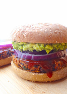 Vegan no crumble black bean burger on a wheat bun topped with mashed avocado, red onion slices and bbq sauce.