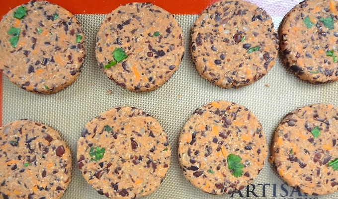 Process step of vegan black bean burger mix shaped into round patties.