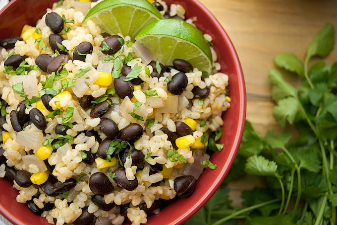 A bowl of black beans and lime rice with lime wedges.
