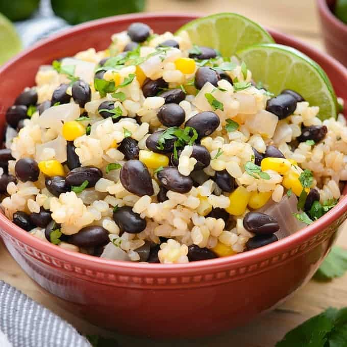 A bowl of brown rice, black beans, corn and onion.