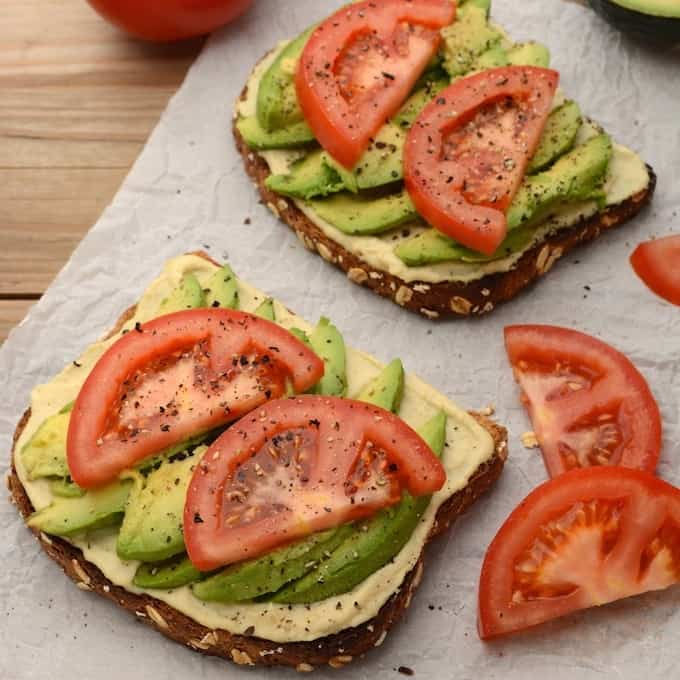 2 slices of hummus avocado toast topped with tomato slices.