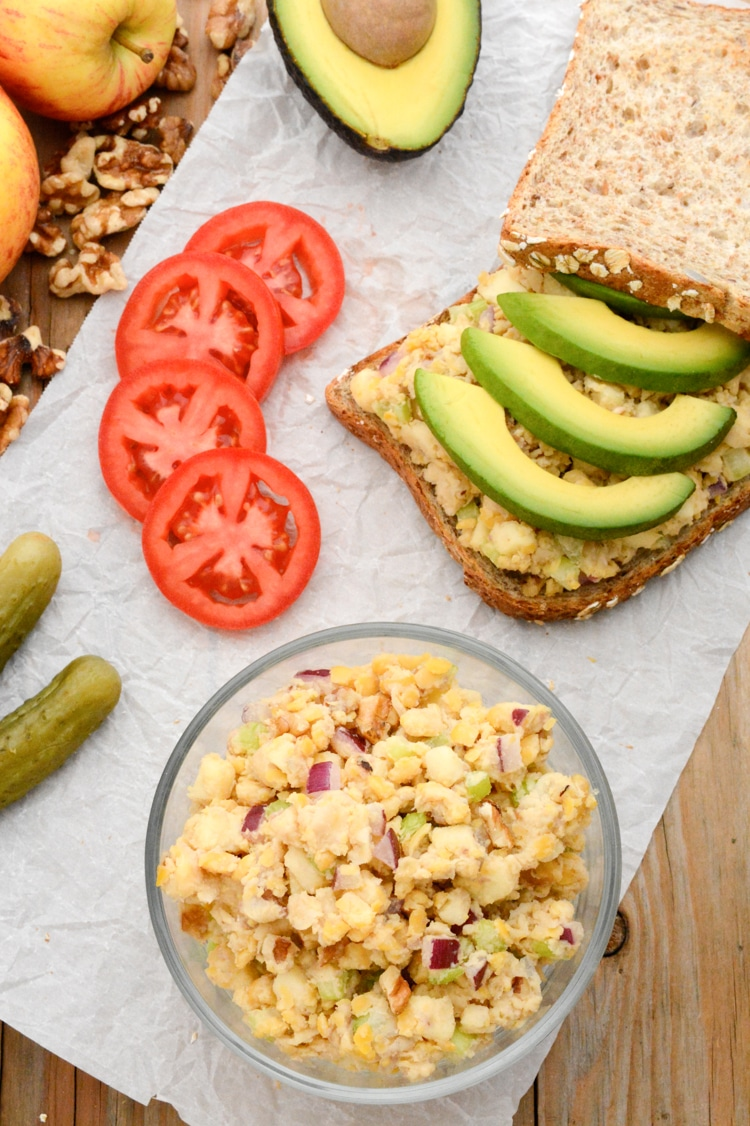 A top photo of the apple-walnut chickpea salad sandwich topped with avocado. The top bread is leaning against the back right corner of the sandwich. It's on white parchment paper on raw wood. There are also pickles, gala apples, tomato slices, walnuts, a bowl of chickpea salad and half of an avocado.