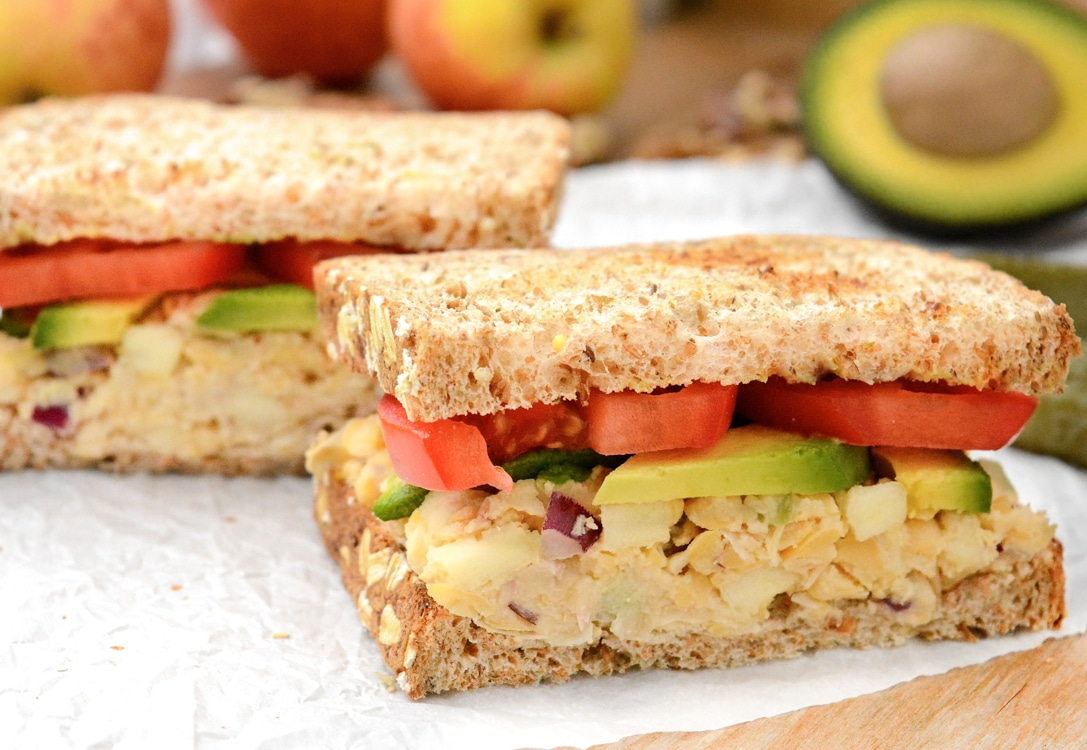 An apple-walnut chickpea salad sandwich topped with avocado and tomato slices. It's cut in half on white parchment paper. There are yellow and red apples, walnuts and half of an avocado in the back.