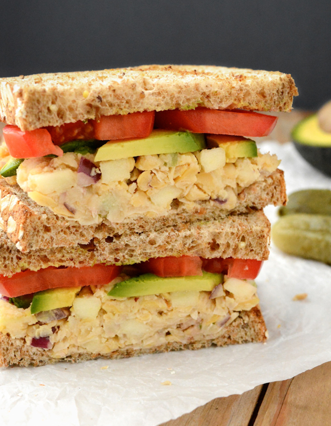 apple walnut chickpea salad sandwich with tomato and avocado cut in half and stack.