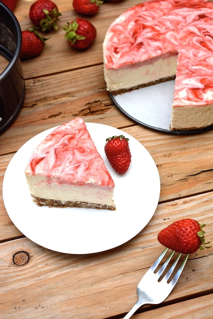 A vegan No-Bake Strawberry Swirl Cheesecake worth hoarding! It has the authentic cheesecake taste without the heavy dairy. This healthier, rich & creamy cheesecake is easy to whip-up, only takes 10 ingredients and includes a fresh strawberry swirl top with extra for drizzling! (vegan, dairy-free, gluten-free)