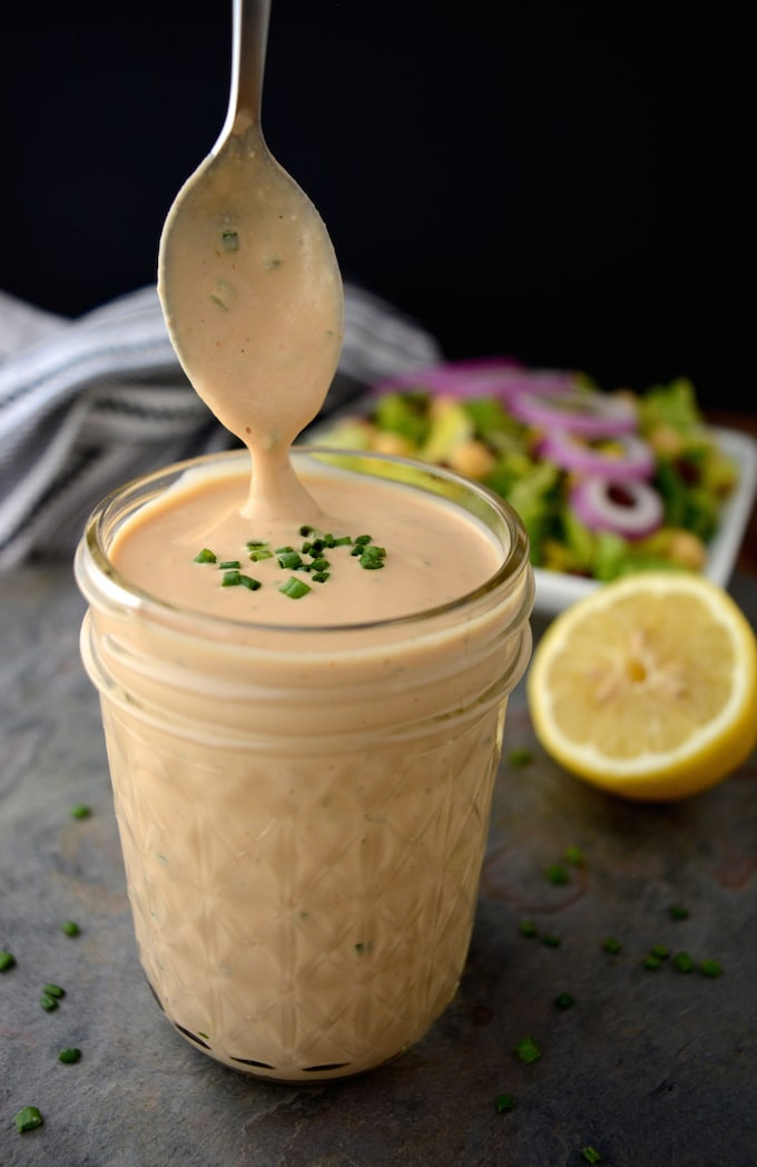 A jar of Creamy Vegan BBQ Ranch Dressing with a spoon being pulled out covered in dressing.