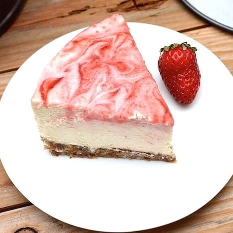 A slice of vegan strawberry swirl cheese cake and a strawberry on a white plate.