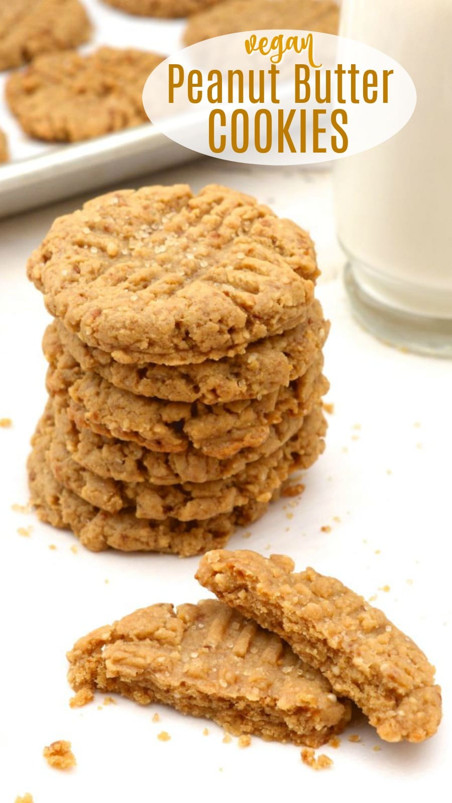 6 vegan peanut butter cookies stacked and one broken with a glass of almond milk.