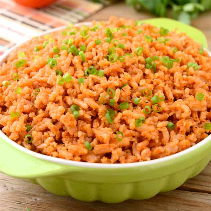 Spanish rice in a green bowl with handles.
