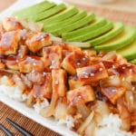 Teriyaki Tofu with avocado slices and caramelized onions on a bed of white basmati rice.