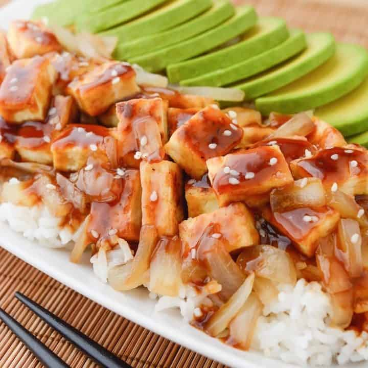 teriyaki tofu and caramelized onions on a bed of white rice with avocado slices.