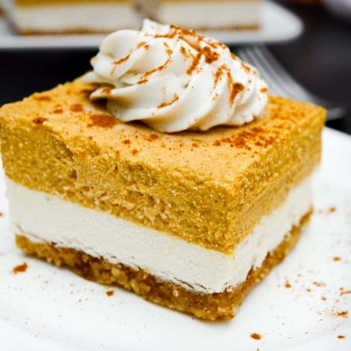 Two layered vegan pumpkin cheesecake bar topped with coconut whip and sprinkled with cinnamon.
