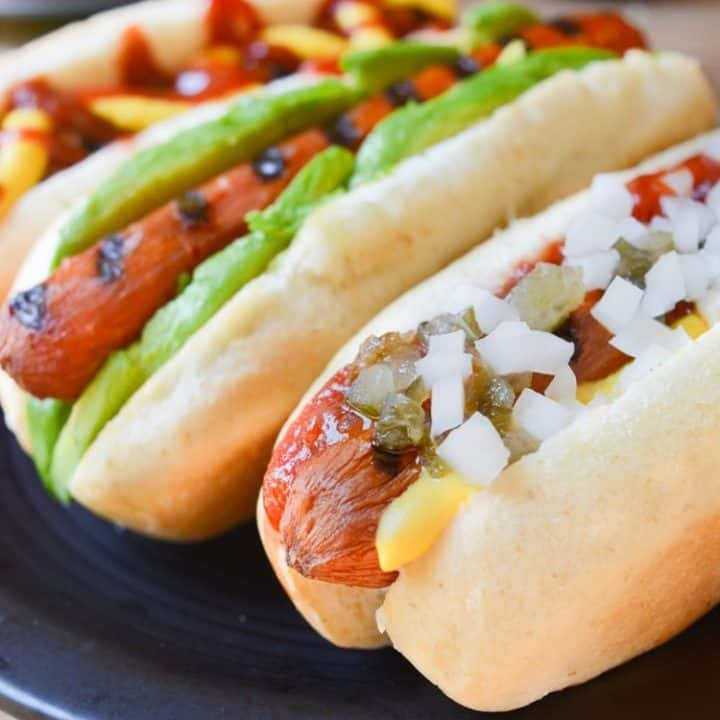 A carrot hot dog topped with mustard. ketchup, relish, and diced onion.