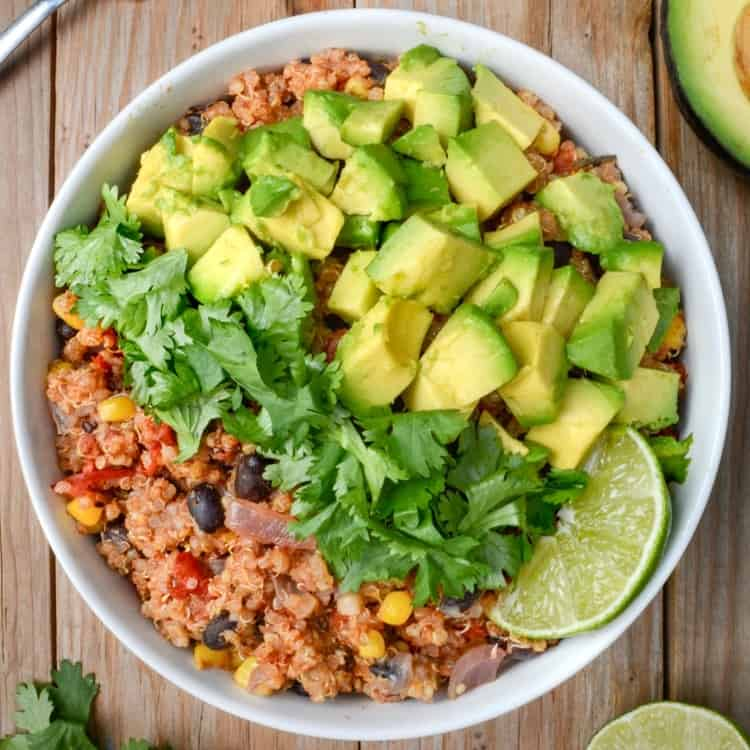 Mexican quinoa bowl topped with fresh cilantro, diced avocado, and a lime wedge.