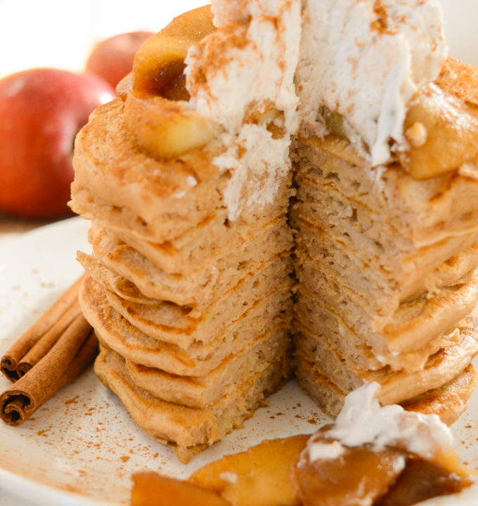 A stack of apple cinnamon pancakes topped with cinnamon apples and coconut whip. A triangle sized pieces has been cut out.