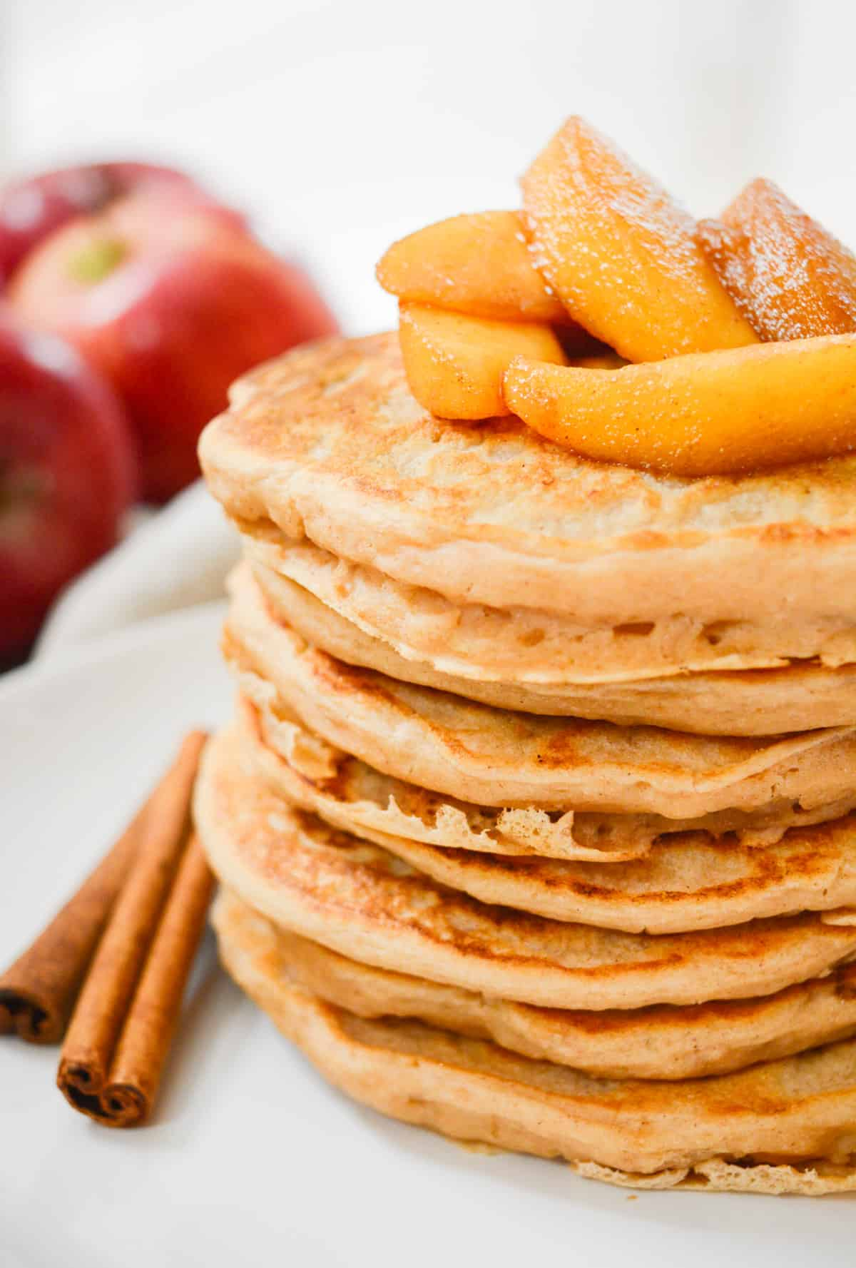 Apple Cinnamon Pancakes topped with cooked apples.