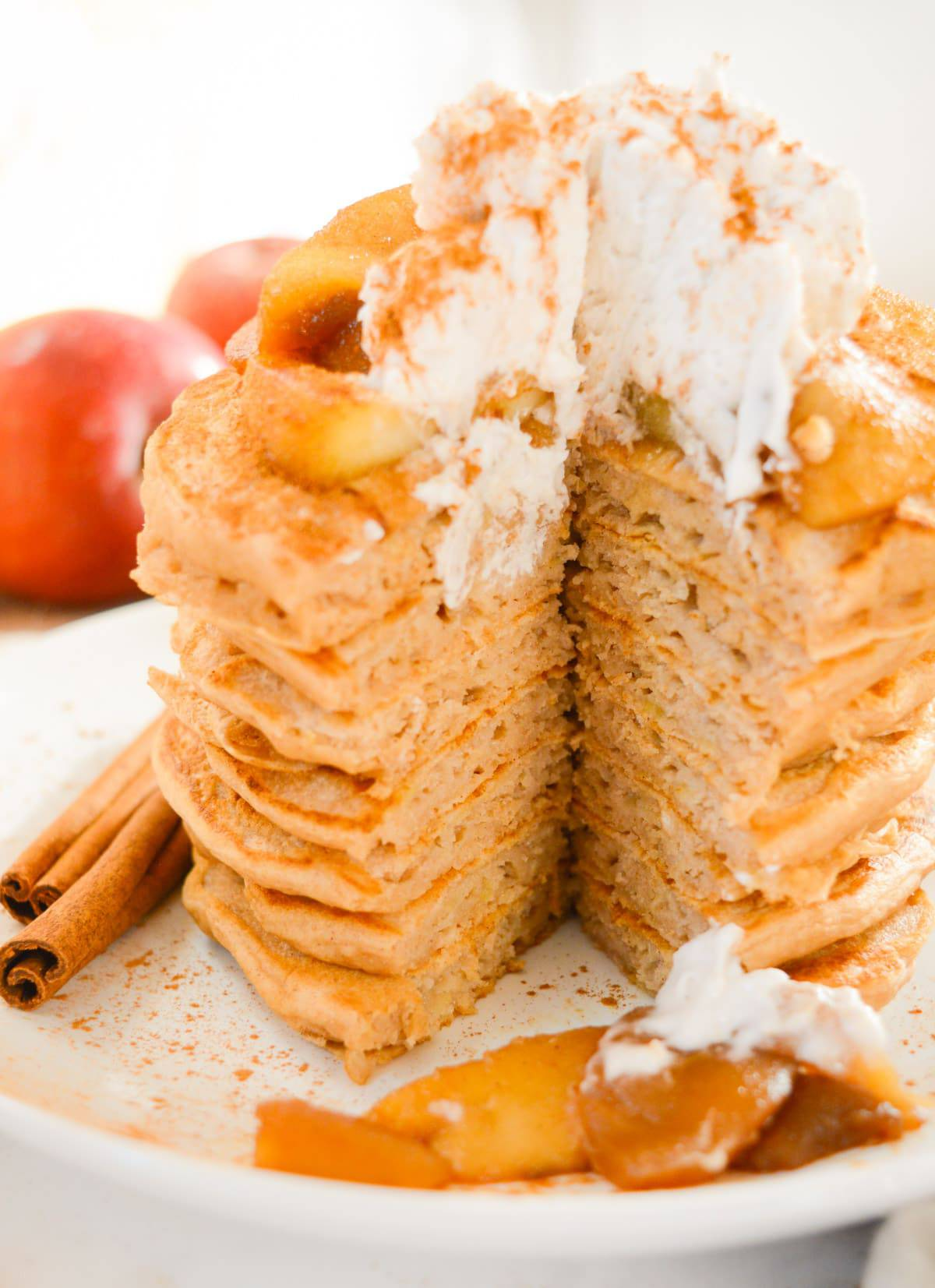 Vegan apple cinnamon pancakes with cooked apples and whipped cream on top and a bite removed.