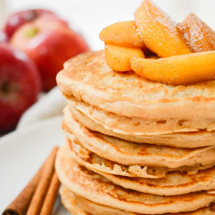 Vegan pancakes topped with cooked cinnamon apples.