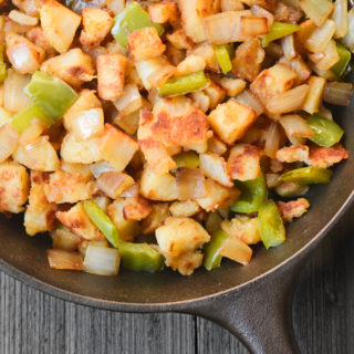 Breakfast potatoes browned in a skillet with bell peppers and onion.