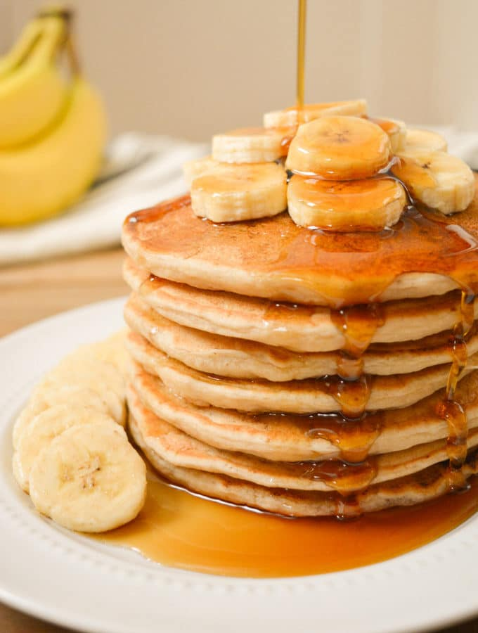 A stack of vegan banana milk pancakes with banana slices on top with maple syrup drizzled on top.