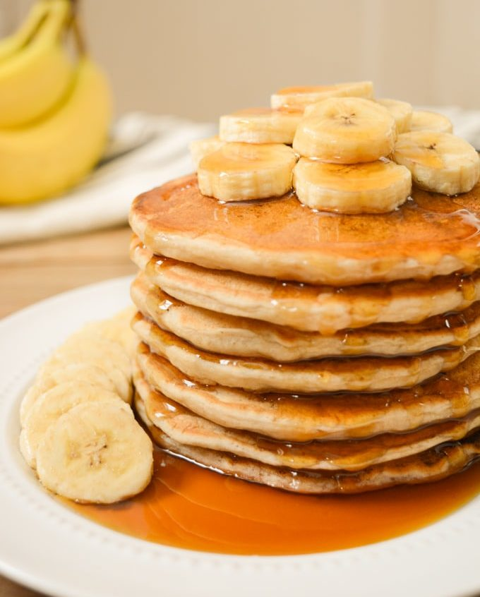 A stack of vegan banana milk pancakes with banana slices on top and maple syrup.
