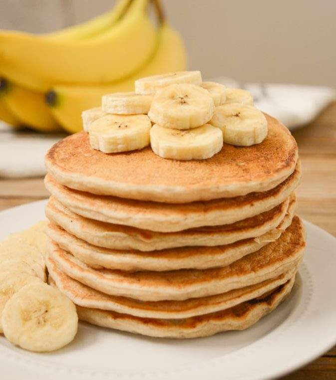 Stack of banana milk pancakes with sliced bananas on top.