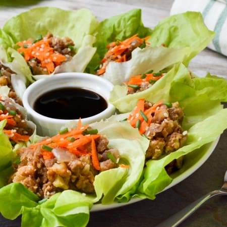 A plate of lentil-walnut filled lettuce wraps with a small white bowl of sesame sauce for dipping.