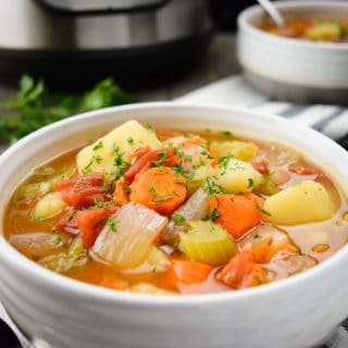 Vegetable Soup in a white bowl with another bowl of soup and the Instant Pot in the back.