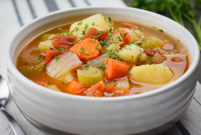 A white bowl of vegetable soup filled with carrots, celery, tomatoes, onion and potatoes.