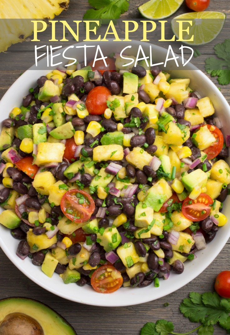 Pineapple fiesta salad in a bowl with avocado, pineapple, cilantro limes and tomatoes surrounding the bowl.
