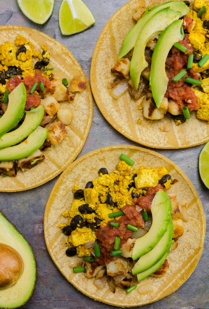 A top angle of 3 vegan breakfast tacos. there are a few cut lime wedges and half an avocado near by.
