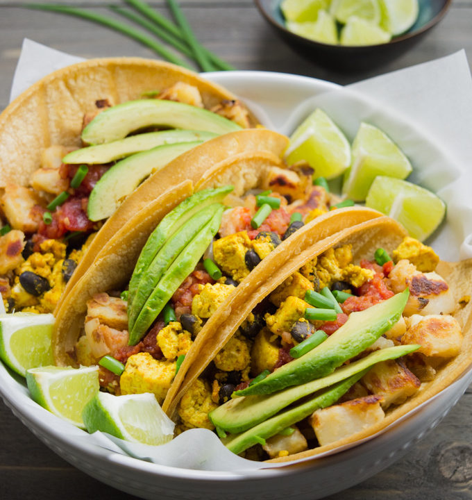 Vegan breakfast tacos in a white bowl with a small bowl of lime wedges.